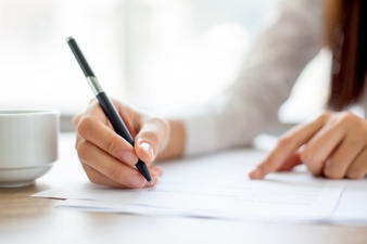 hand-of-businesswoman-writing-on-paper-in-office_1262-2119